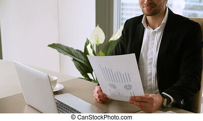Handsome male boss studying statistic report, satisfied with...