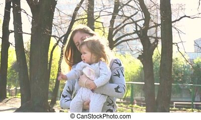 Mother with baby outdoor in spring time in slowmotion