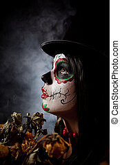 Sugar skull woman in tophat, holding dead roses, studio shot...