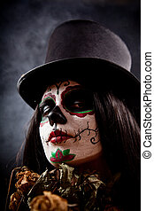 Sugar skull girl in tophat holding dead roses, studio shot