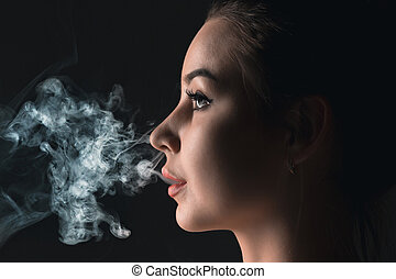 The face of vaping young woman at black studio - The face of...