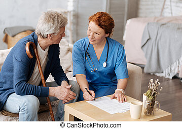 Private nurse and elderly man discussing the contract -...