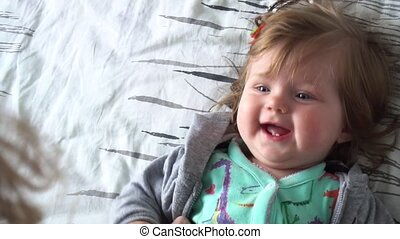 Cute baby girl smiling lying on bed at home