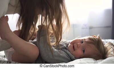Mother playing with baby girl in bedroom