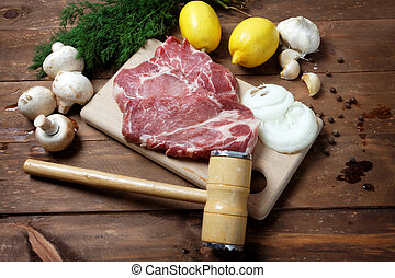 pork steak and mallet - Raw pork steak and mallet on vintage...