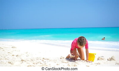 Adorable little girl playing with beach toys on white sandy...