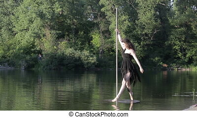 Woman is dancing on a pole in nature.