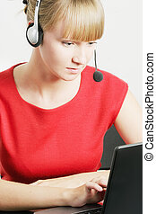 Call center employee looking at laptop - Young blonde call...