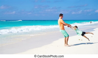 Father and his adorable little daughter at tropical beach -...