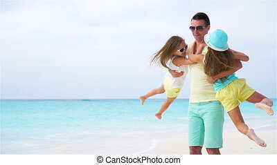 Father and his adorable little girls have fun together at tropical beach