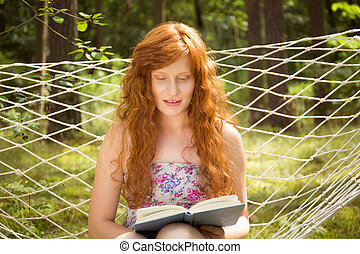 Woman reading on a hammock in the garden - Ginger woman...