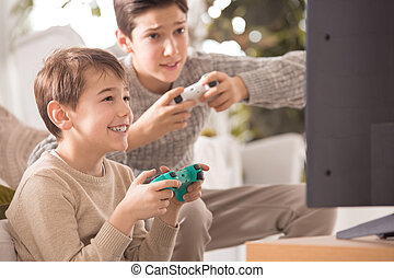 Boys playing videogame - Two boys playing a video game on...