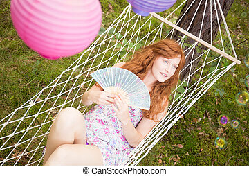 Ginger woman lying in a hammock - Young ginger woman lying...