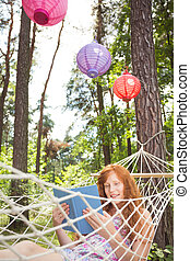 Ginger woman reading in a hammock - Ginger woman reading a...