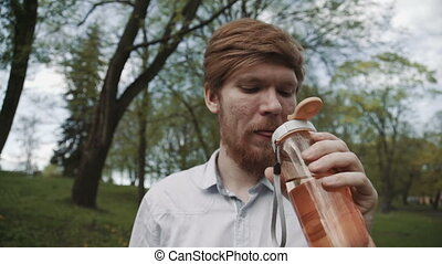 Redheaded young man with a beard drinking water from bottle. Cold drink summer day outdoor. Young fit man drinking water. Healthy lifestyle drink water.