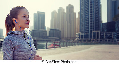 happy woman with earphones running over dubai city -...