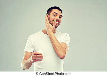happy young man applying cream or lotion to face - beauty,...