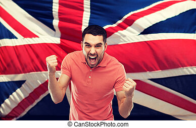 angry man showing fists over brittish flag - emotion,...