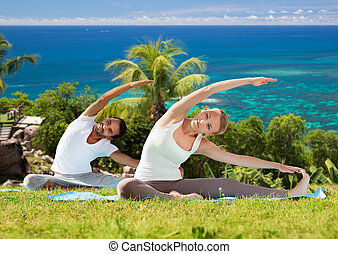happy couple making yoga exercises outdoors - fitness,...