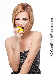 young woman biting on a whole lemon - a frontal portrait of...