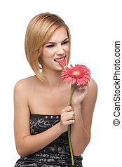 a portrait of a young, blonde woman, playing with a red flower she holds with both her hands, biting on it's petals, with a funny expression on her face, showing her teeth