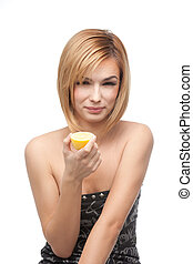 young woman tasting a lemon - portrait of a young, blonde...
