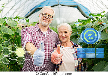 happy senior couple at farm showing thumbs up - organic...
