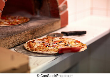 baked pizza on peel and oven at pizzeria - food, italian...
