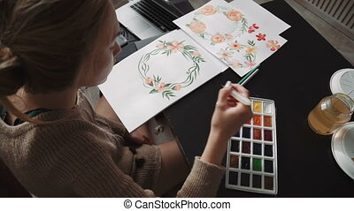A young woman artist, paints with watercolor paints a water...