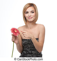 a portrait of a young, blonde woman, picking pettals of a flower she holds in her hand, smiling, with a happy expression on her face