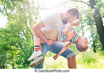 Young father with little son in green woods, sunny day. -...