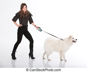 young woman walking a white dog viewed from a side - a...