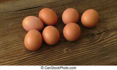 Brown eggs on wooden board