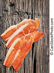 Smoked Pork Ham Prosciutto Slices on very Old Wooden Surface...