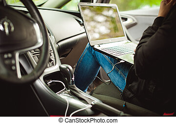 Professional man with a laptop in car tunes tuning control system, updating software, gaining access through to computer, sitting in cabin