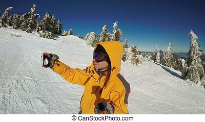 Girl is taking pictures of herself on skis