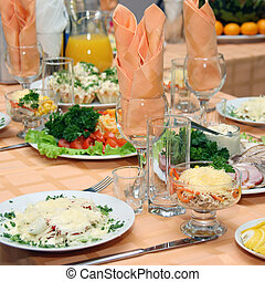 Table covered at restaurant with salads in the foreground