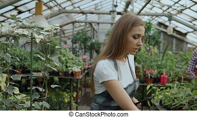 Dolly shot of Young woman working in garden center....