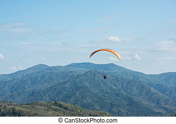 Paragliding in mountains. Para gliders in fight in the...