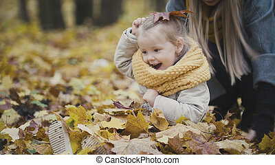 Mother and her daughter little girl playing in a autumn park - throw the leaves, baby laughter