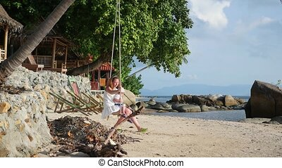a girl and a child swinging on a rope swing on the beach