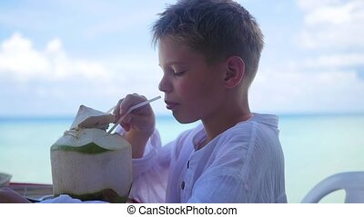 a young man in a cafe drinking a cocktail on terrace. outdoors.