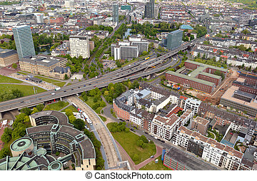 High top view of long motorway and many roofes of city...