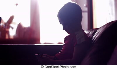 Silhouette of a young boy playing game on smartphone in home