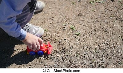 A child is playing with a toy car on the sand