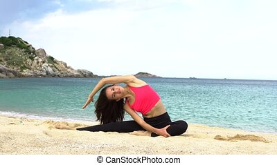 Young sporty woman does stretching exercise on the beach near the sea. Healthy active lifestyle concept.
