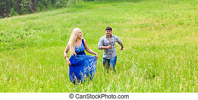 Young man and woman running on countryside meadow with green...