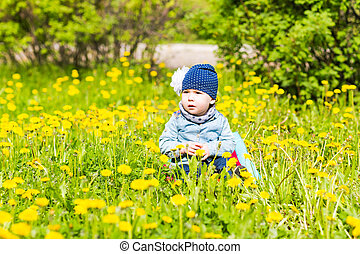 Beautiful happy little baby girl sitting on a green meadow with yellow flowers dandelions on the nature in the park.