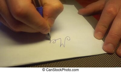 Man hand writing merry christmas with black pencil on white paper. Top view