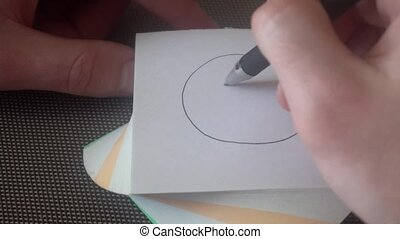 the hand of the young man draws a sad face,then crossed out,tears off the page and draws a smiley face